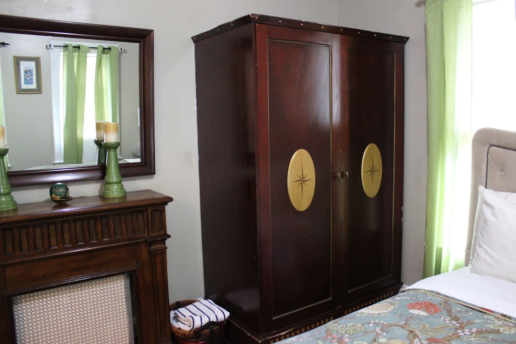 Antique armoire equipped with extra clothes hangers, iron, and ironing board in Private Bedroom #1 on the first floor.