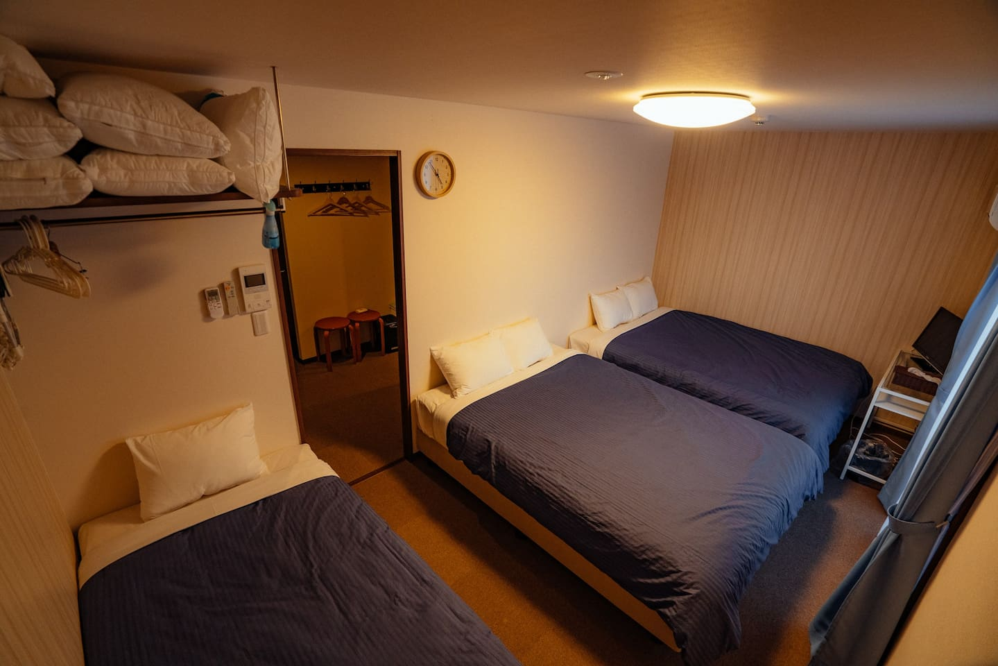 Bedroom with two full/double size beds and one twin/single bed.