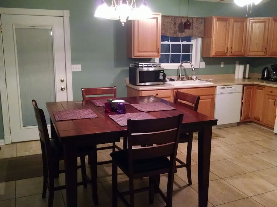 Kitchen with dining table & chairs, microwave, dishwasher, oven, stove, refrigerator, coffee maker, electric water boiler, and deck access.