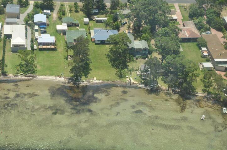Aerial view of Island View Waterfront (2nd house from left) and neighbours, showing large grassy area and sandy waterfront