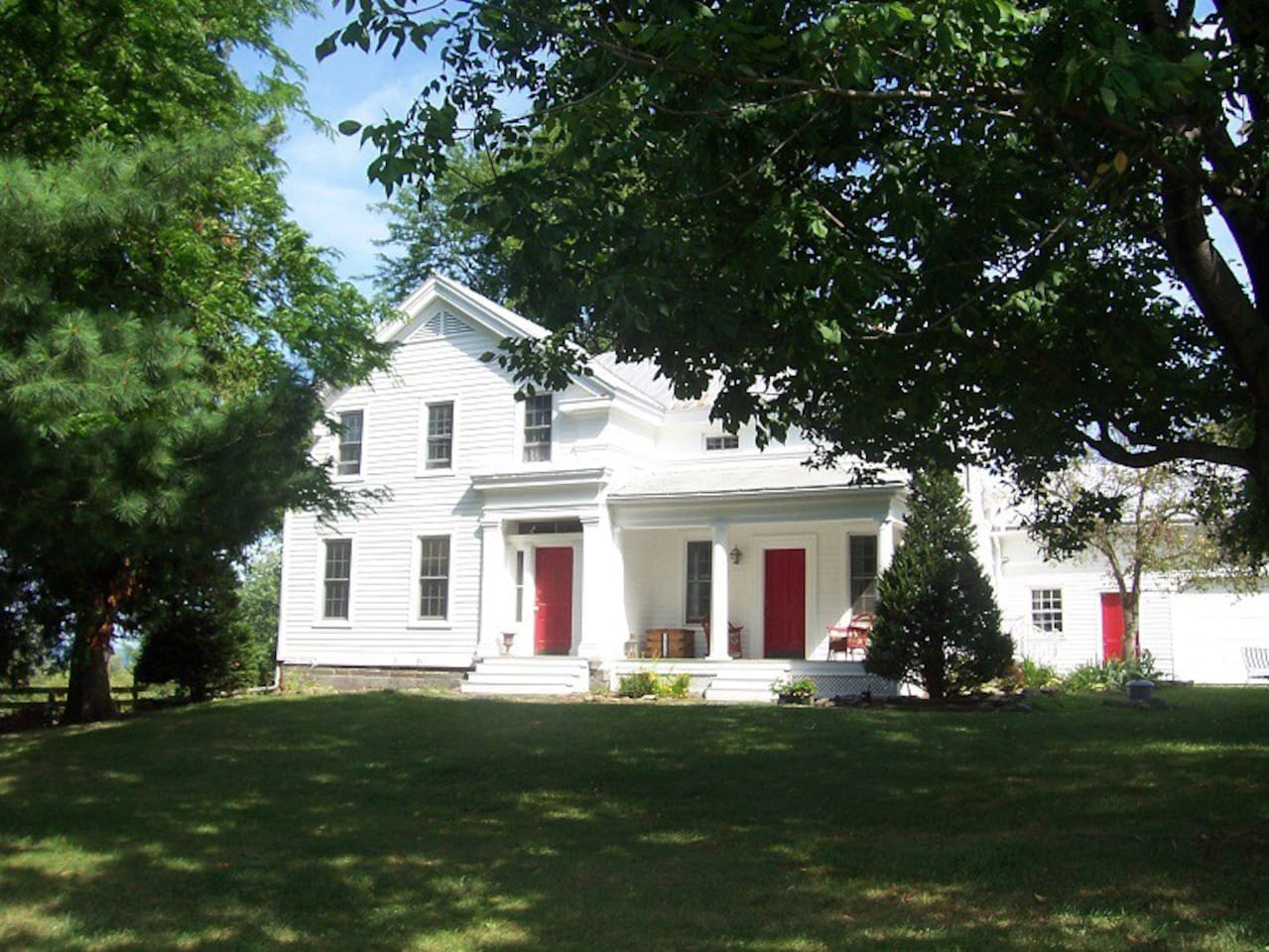 Our historic 1845 Greek Revival farmhouse on a beautiful summer day. We are an Airbnb Superhost and we have earned a 2015 Certificate of Excellence from Tripadvisor and we are a Tripadvisor GreenLeader.