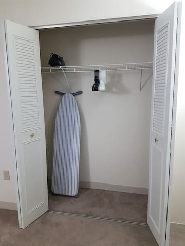 Closet with iron board, iron and hangers.
