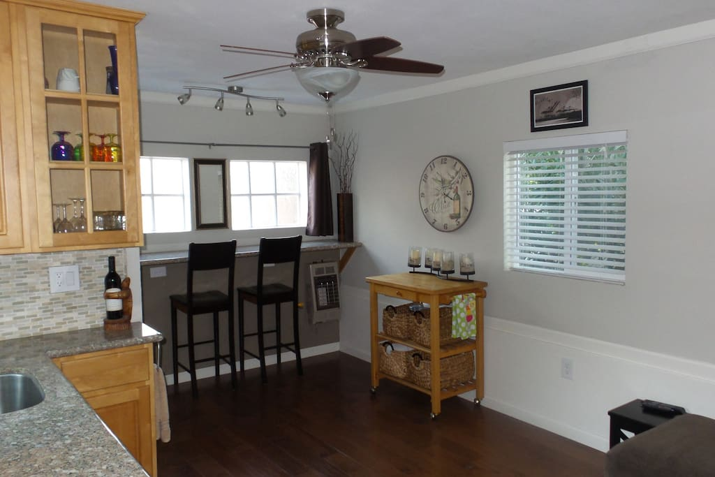 Hardwood floors, lots of natural light, ceiling fan, and sitting bar.