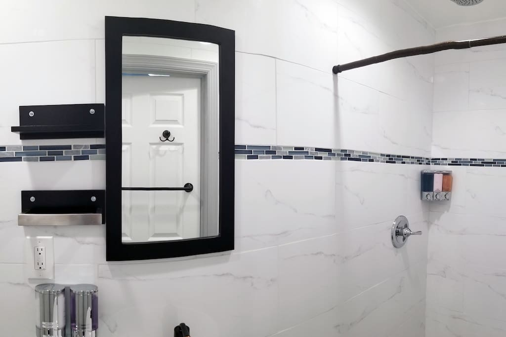 Stylish contemporary bathroom with chrome toiletry dispensers
