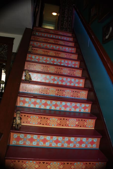 entranceway staircase is lit by colored LED lights under the banister causing interesting color shifts on the designs.