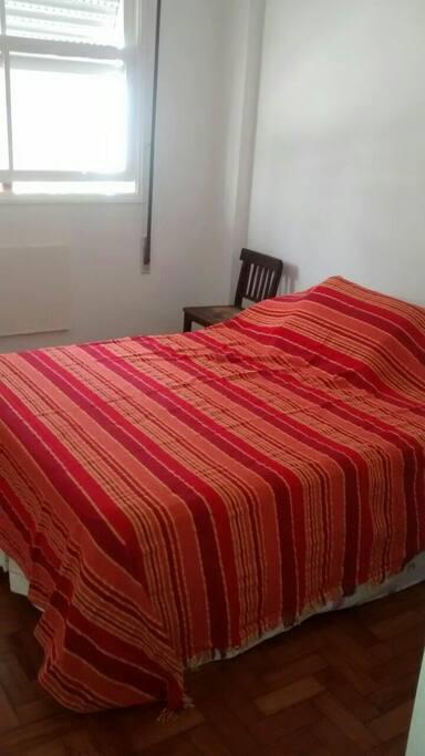 Mostra o quarto com cama de casal.