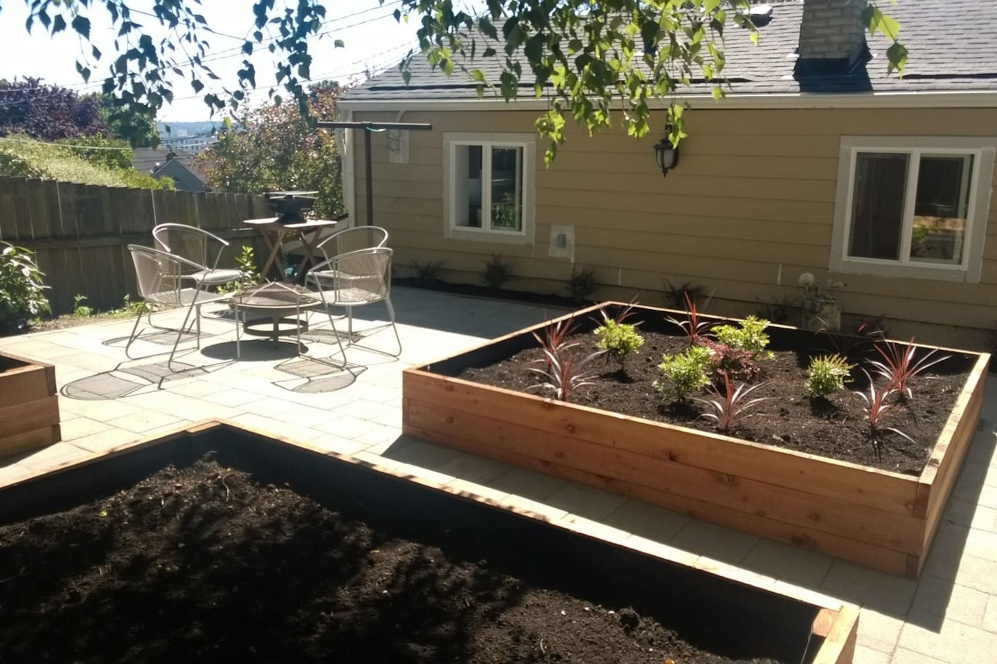 Newly renovated patio with planter boxes, herbs, flowers, fire pit, and hibachi!