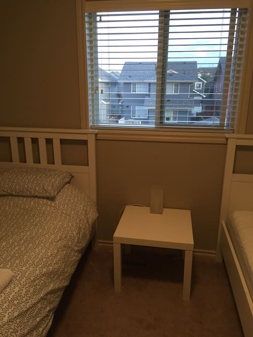 Room also features a bedside table with lamp, and a large window to let in fresh air and lots of natural light.