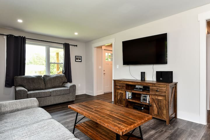 Front door in the back of the photo opens to a coat rack and then into the living room. All TVs include Netflix. A DVD player and an assortment of DVDs are included.  Want to listen to music?  Bluetooth sound system included.