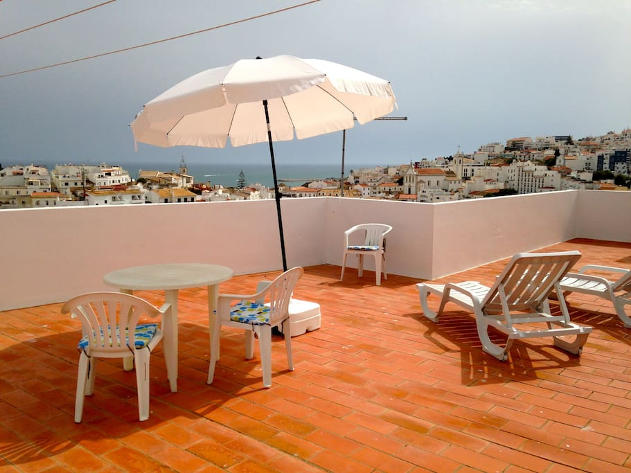 Rooftop Terrasse with chairs, table and sunbeds