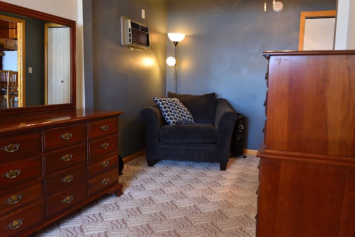 One of the bedrooms is downstairs.  It has a queen bed, 2 dressers, a full closet, a/c, and an extra large chair for lounging.  Fully carpeted with ample lighting options, 2 ceiling fans, floor fan, heater, and a large mirror.