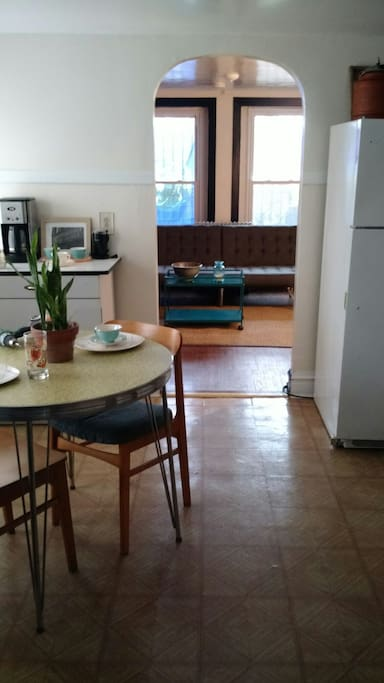 View from kitchenette into living room (photos don't reflect new kitchen floor!).  While this is technically a garden apartment, it's more ground-level than below ground.  Great south and west light in the main living spaces! The bedroom can be accessed from the kitchen or living room, and the bathroom is also through the kitchen.  It's a cozy space for one or two for a long stay, or 2-5 people for a shorter stay with a busy schedule outside the apartment!