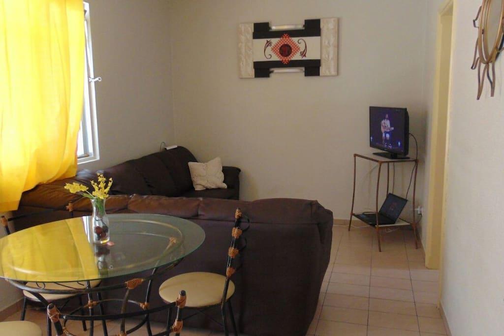 Sala ampla com mesa e TV
