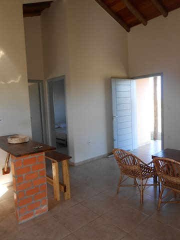 Sala ampla, com teto alto e móveis rústicos.