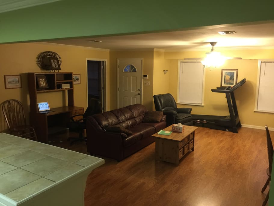 This is the living room as seen from the kitchen. You can see the treadmill, furniture and table here.