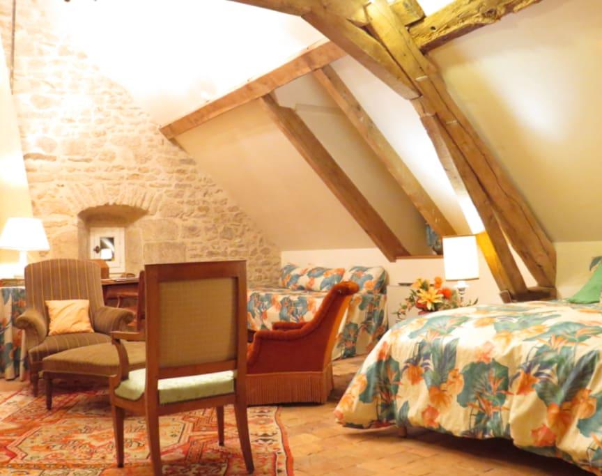 Grande chambre composée d'un grand lit et d'un petit lit, avec coin salon