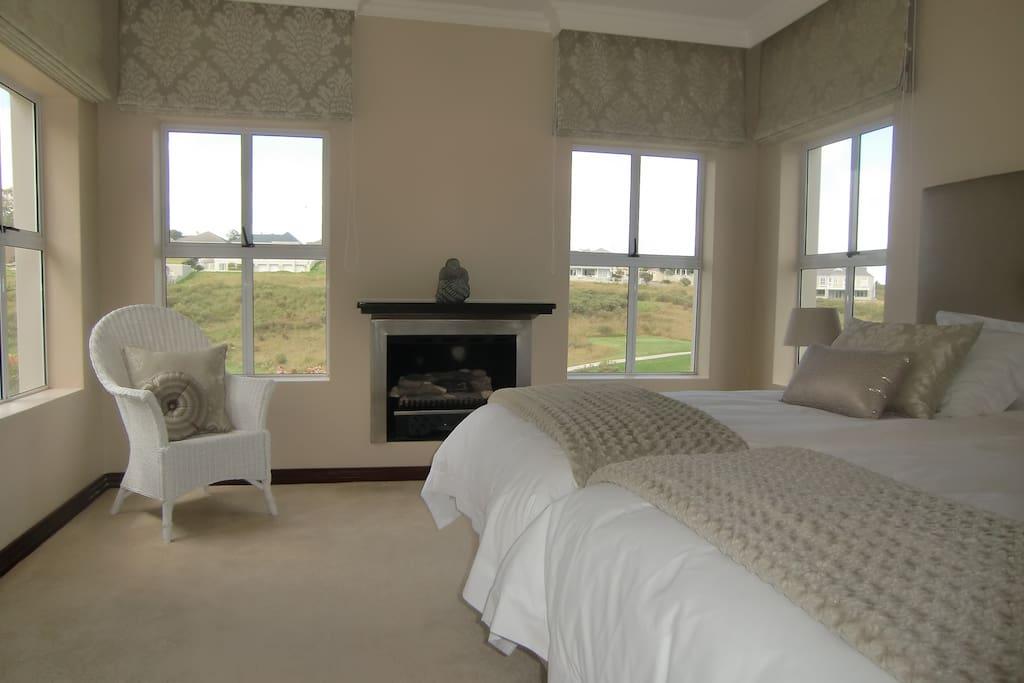 Mainbedroom mit 4 großen Fenster und einer Terassentür zum Garten und zum Pool. Blick auf das Fairway, Garten und die Mountains.