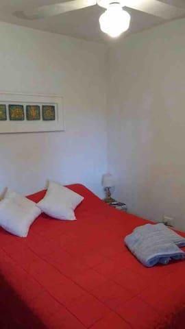 Dormitorio con cama matrimonial y una cama de una cuna grande.