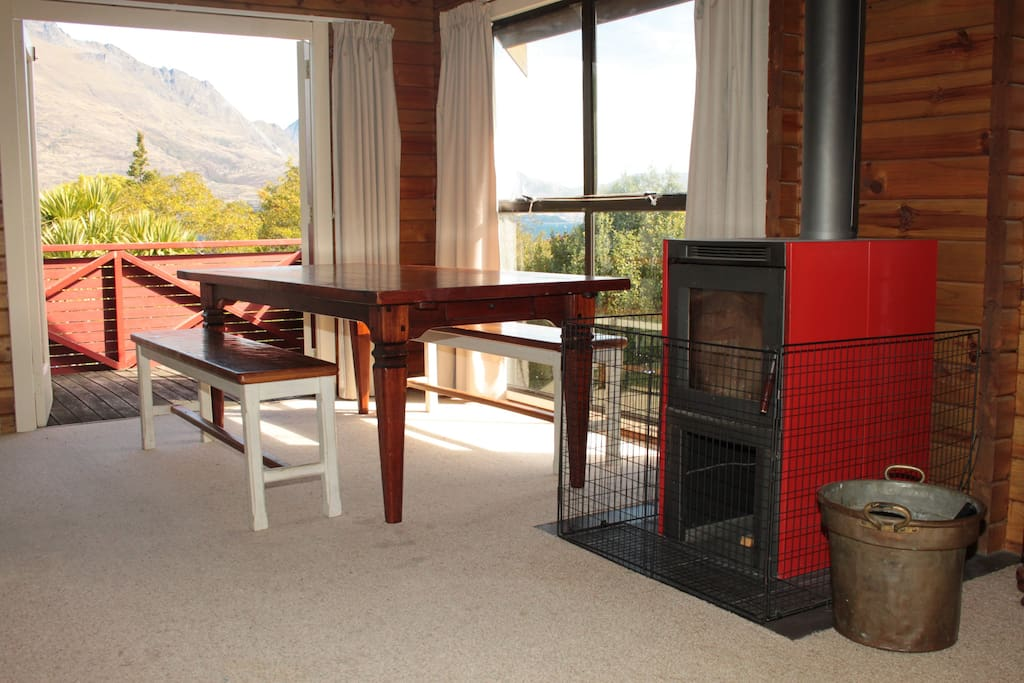 Living area: Woodburner, large dining table, balcony