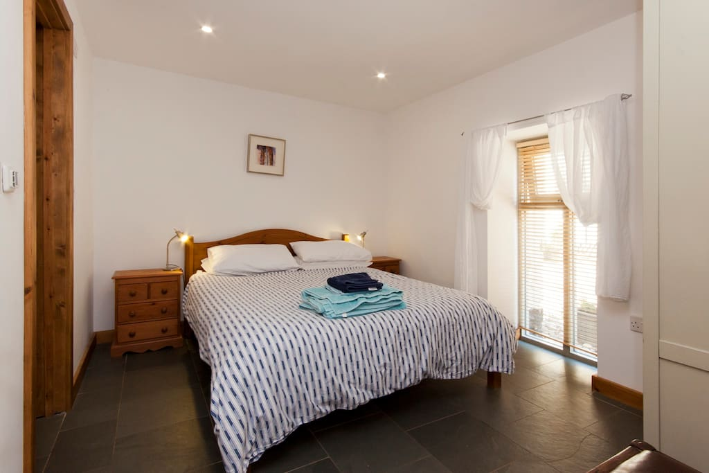 The master bedroom has heated slate flooring and a kingsize bed