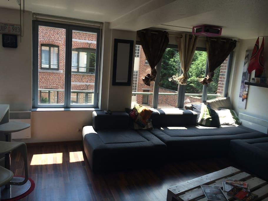 Salon ouvert, canapé d'angle pouvant servir de couchage