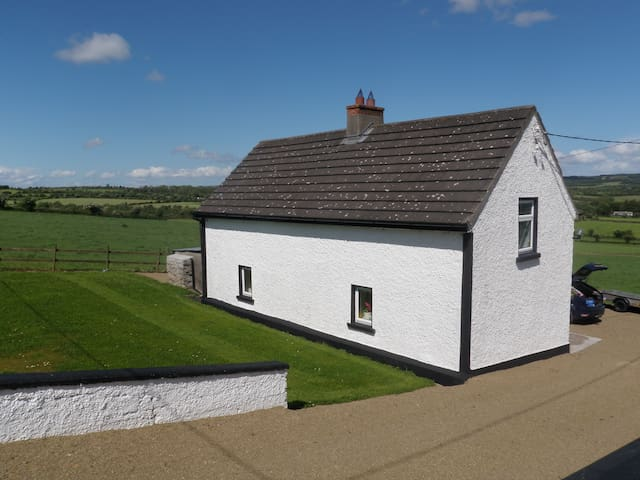 View of the cottage from roadside showing lawn behind and countryside views all around!