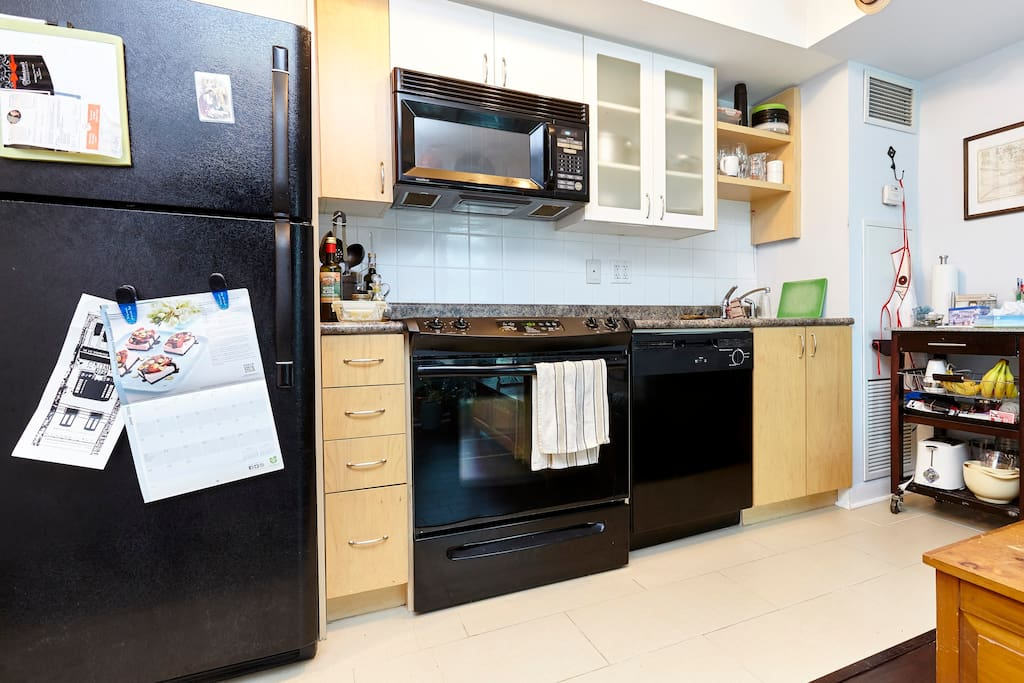 Kitchen fully equipped with microwave, stove, dishwasher, toaster, kitchen stuff for cooking.
