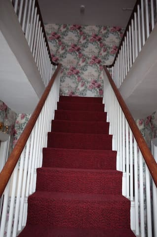 Front hall stairway leading to your suite