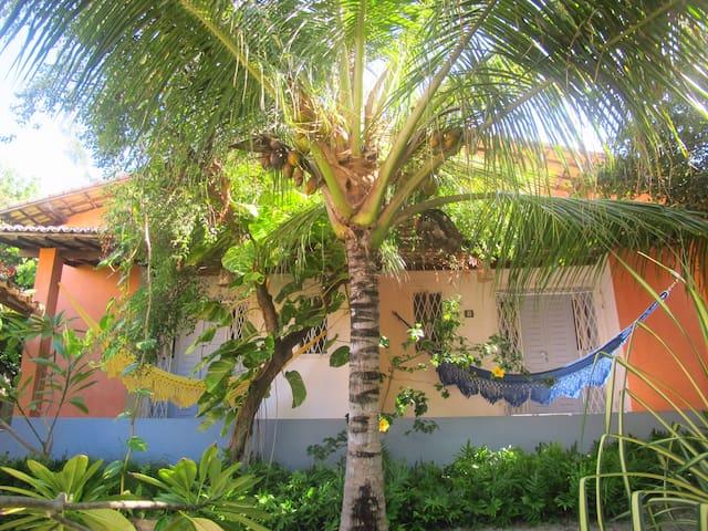 Vista da fachada, varanda com redes rodeado por um belo jardim tropical.