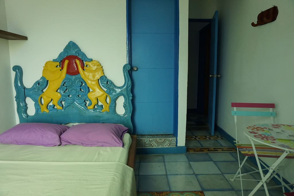 Room decorated with beautiful tiles a matrimonial bed and a table