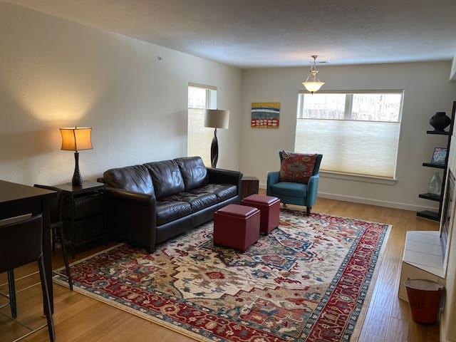 Living room and dining area have wood floors and comfortable seating.