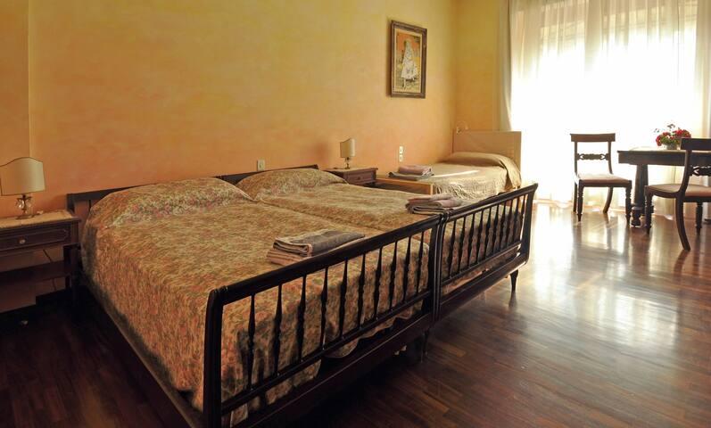 Stanza disposta con letto matrimoniale e un letto singolo
