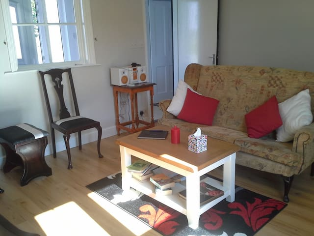 Sitting area of Farm Cottage, books, games, radio as you relax in front of an open turf fire.