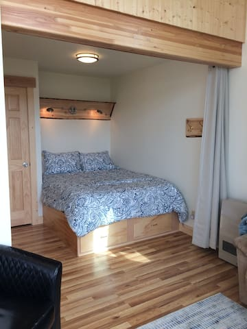Queen size bed with custom built-in storage underneath.