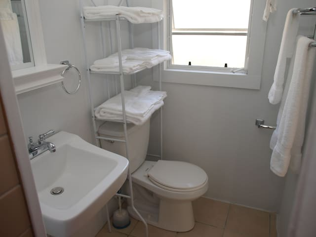 Bathroom features a standup shower stall and lots of fresh towels.