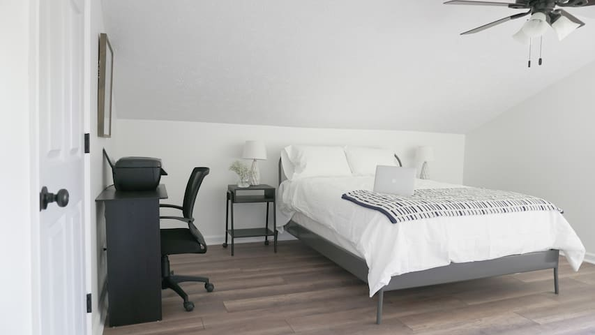 Spacious upstairs bedroom features a queen-size bed and desk with printer for your needs.
