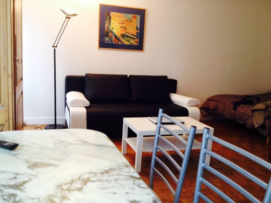 Salon équipé d'un canapé convertible design 2 place, d'une table en marbre avec 4 chaises, internet, 2 grands placards de rangement libres.