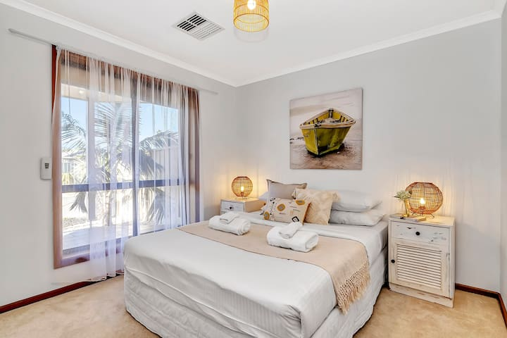 A third bedroom is very well lit and has a queen bed dressed in high-quality linen, bedside tables and charming decor