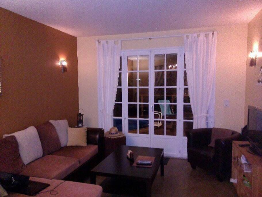 Salon dont la baie vitrée donne directement sur la terrasse en bois et la piscine