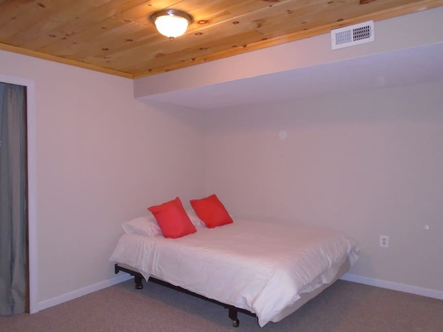Spacious Bedroom with Queen Bed, Featuring Cozy Natural Wood Ceiling.