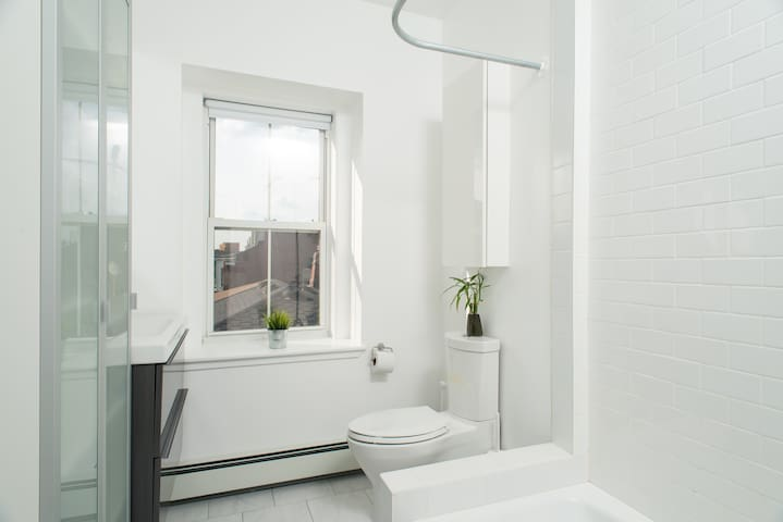 Common bathroom. Clean and white subway tiles, and cast iron tub.