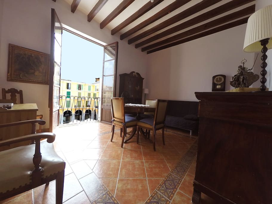 Living room decorated with part of the original furniture, more than 100 years, with window to Plaça Major.