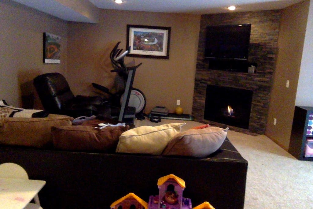 Basement entertainment room with exercise equipment and gas fireplace