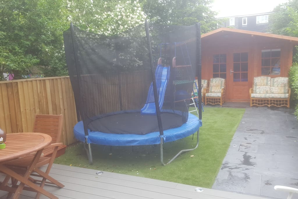 Backyard with patio and trampoline and slide