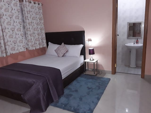 Bedroom 2: Ensuite bedroom fitted with a double bed, wardrobe, air conditioner, ceiling fan, bedside unit and lamp