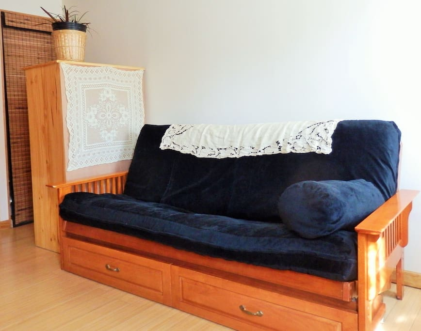 Full sized futon bed with storage drawers underneath. On your left, dressing corner with large wood dresser and closet.