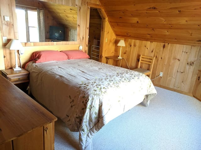 bedroom with queen bed, air conditioner, and view of the lake