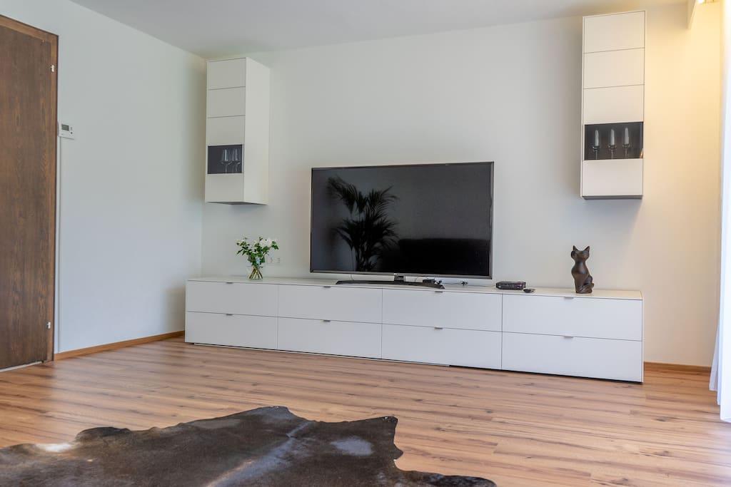 lichtdurchflutetes Wohnzimmer mit extragroßem (60 Zoll) 4k Fernsehgerät, Kabelanschluss sowie WLAN