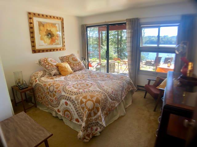 Queen bedroom with sliding glass doors to patio