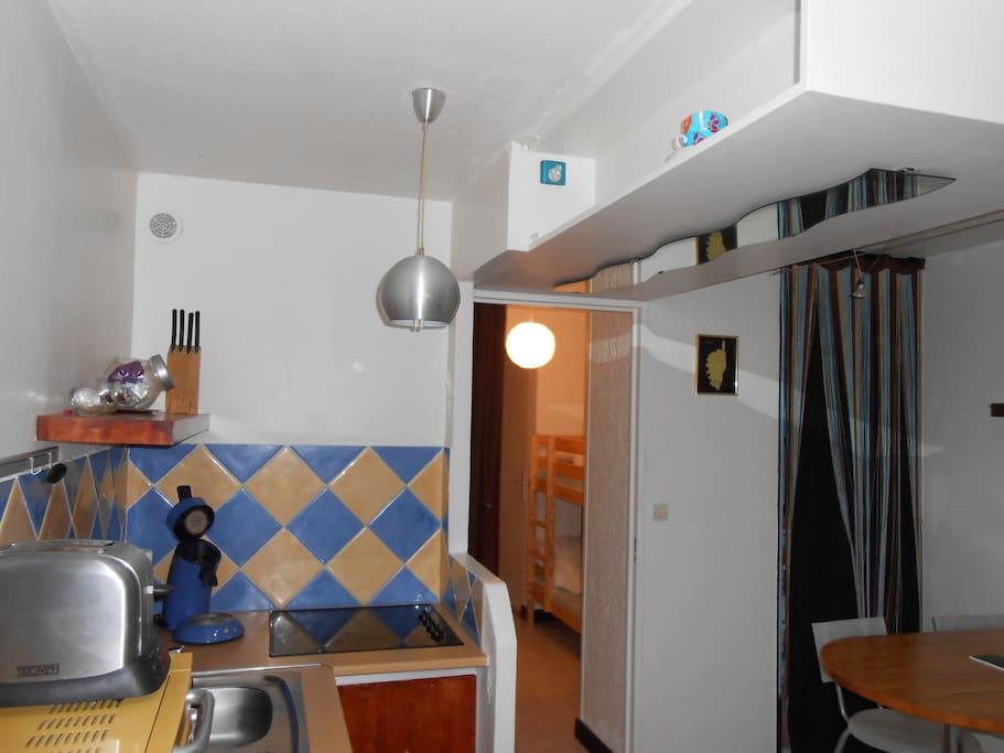 On y voit la cuisine, table bar,lits superposés.